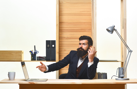 Business, people and technology concept - serious businessman working in office with laptop. Busy salesman or broker working in office. Business man. Successful businessman sitting at workplace. CEO.