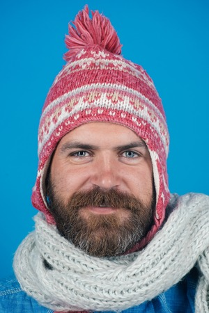 Men winter fashion. Handsome trendy man wearing knit hat and scarf. Portrait of smiling bearded man with scarf and hat on blue background. Young man with scarf and hat in autumn, winter time.