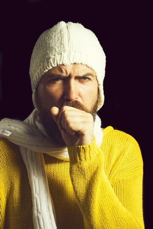 Sick man in sweater, hat and scarf while having cough has cold and flu, winter style clothes. Concept of chronic cough. Medication, treatment and healthcare concept. Attractive guy and health problems