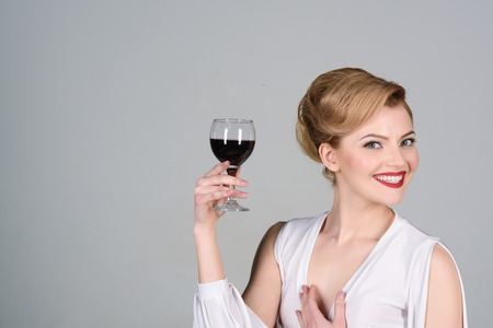 Gorgeous blond woman with glass of wine. Beautiful sensual girl with stylish makeup and retro hairstyle in white dress tasting red wine. Sexy smiling woman tasting wine. Isolated on grey background.