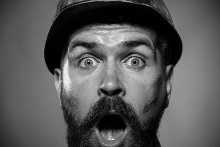Man builder. Portrait of mechanical worker. Construction worker in hard hat. Portrait bearded man with protect helmet wearing. Black and white. 스톡 콘텐츠