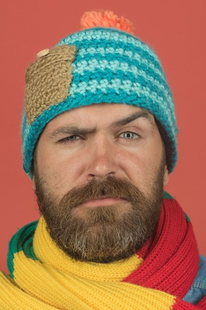 Men autumn/winter fashion. Serious man wiht beard wearing warm scarf wrapped around his neck, hat on head. Handsome bearded man wearing autumn or winter clothing. Closeup portrait.
