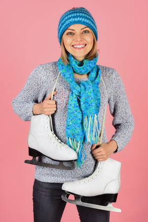 Winter fashion, sport style. Smile woman skater with figure skates in hat, scarf and sweater. Vacation, holidays, lifestyle - girl with ice skates getting ready for ice skating, winter sport activity.