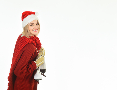 Smiling girl in santa claus hat gets ready for ice skating. Ice skating girl. Woman in winter clothes with ice skates. Winter sport. Woman in Santa hat, red sweater&gloves with ice skates. Copy space. Stock fotó
