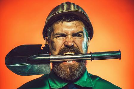 Industriearbeiterschutzhelm mit Spaten. Baumeister, Bauarbeiter mit Spaten. Mann im Helm mit Schaufel. Handwerker, Händler, Maurer halten Schaufel in den Zähnen. Männlicher Arbeiter mit Schaufel. Standard-Bild