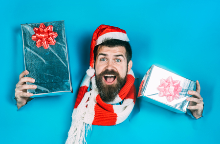 Gifts for whole family. Man with gifts peeking from hole paper wall. New year, Christmas presents. Black friday. Discount, season sales. Santa Claus with gifts making hole in paper holds gifts in hand