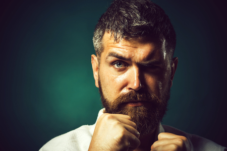 Portrait boxer before fight, closeup. Bearded man do karate training. Strong angry bearded man dressed in kimono, shaking fist. Strong focused professional karate instructor. Copy space for advertise. Stock Photo