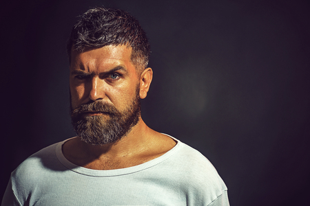 Serious unshaven man. Serious man with beard and mustache in white t-shirt. Stylish man with beautiful hairstyle. Fashion male portrait. Handsome athlete bodybuilder. Athlete mma fighter tough boxer. Stock fotó
