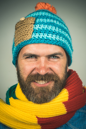 Smiling fashionable handsome bearded man in winter scarf and hat. Attractive man with scarf and hat in autumn/winter time. Men autumn/winter fashion, european style. Guy in trendy casual cap and scarf
