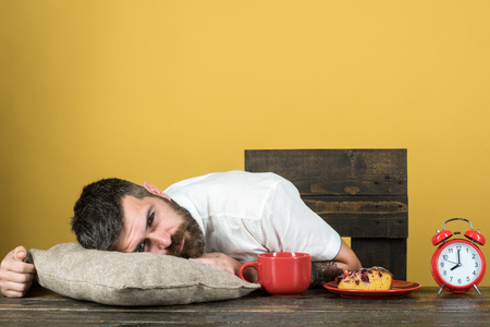 Exhausted man resting at table on pillow with alarm clock and cup of coffee on kitchen. Tired bearded man sleep at table after long hours at work. Overworked businessman sleep on desk at breakfast.