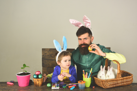 Father and her child enjoy painting Easter eggs. Happy easter ideas for family.