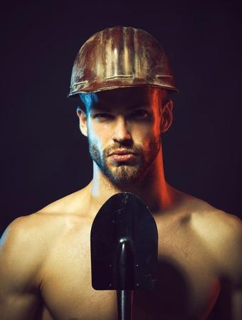 Sexy builder, repairman in protective hart hat with spade. Construction & industry concept - professional builder, engineer, repairman with safety equipment. Construction worker in helmet with shovel. Stock fotó - 108893210