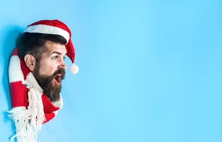 Surprised man looking through hole in blue paper. Bearded man in Santa hat& scarf making hole in paper. Surprised Santa Claus looks through hole in paper wall. Copy space for advertise. Discount, sale