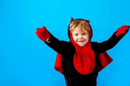 Halloween or horror concept. Cute boy in devil costume. Halloween party. Holiday Halloween. Funny child in carnival costumes devil. Halloween theme, decorations. Cheerful toddler in vampire costume.