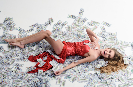 Millionaire woman lying in money. Currency, women, winning. Sexy woman lying in dollar bills. Girl in elegant red dress lying in banknotes. Rich woman lies on money. People, dollar, money, wealth&rich