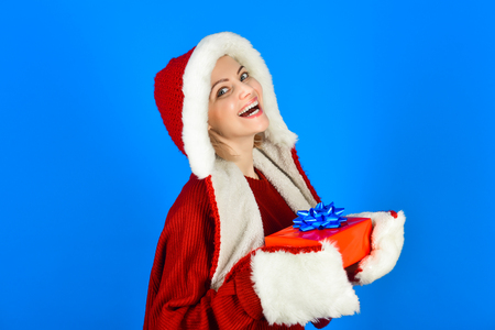 Happy woman in santa hat holds Christmas present. Excited woman in santa claus hat with gift box. Beautiful sexy woman in santa clause costume. Beauty Christmas fashion model girl with X-mas gift box. Stock Photo