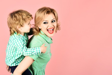 Happy family. Mother and son smiling. Blond mother holding boy on piggyback. Family time together. Motherhood concept. Mom and toddler having fun together. Little kid express love to mommy. Copy space Standard-Bild