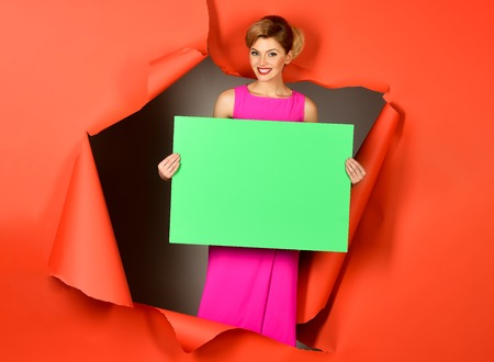 Emotional happy girl passes through hole in red paper. Sensual blonde model in pink dress holds empty green board for your advertising slogan. Copy space for advertise. Trendy clothes. Fashion product