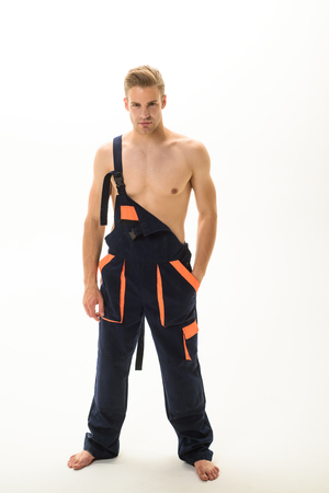 Sexy muscular laborer with nude torso in overalls. Strong builder, industrial worker, mechanic wears coveralls.