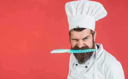 Cook with knife. Angry chef with knife in mouth. Bearded chef in white uniform holds sharp knife in teeth. Professional chefs knives.