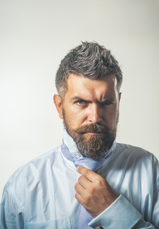 Bearded man in shirt dressing up, adjusts tie on neck. Businessman in formalwear adjusting necktie. Business, fashion, men style, clothes concept. Handsome businessman dressing up. Daily lifestyle.