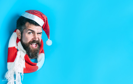 Winking guy in Santa hat breaks through paper wall. Happy man in Santa hat looking through hole in paper. Christmas, New Year, holidays, winter concept. Stylish guy in santa hat&scarf. Christmas sales Stock Photo