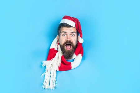 Surprised Santa Claus looking through hole in paper. Man in Santa hat. Winter holiday. Christmas celebration. Merry Christmas and Happy New Year. Christmas shopping concept. Christmas sales. Discount.