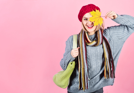 Autumn mood. Autumn time. Woman hides eye by yellow leaf. Woman with autumn yellow maple leaf. Autumn fashion. Smiling woman with autumnal leaves. Season sale. Discount. Sale. Copy space. September.