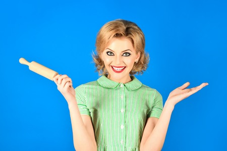 Happy housewife with rolling pin. Woman in pin up style holds rolling pin, smiles. Beautiful pinup girl with perfect makeup with rolling-pin. Blonde woman, gorgeous girl hold rolling pin. Retro theme. 免版税图像