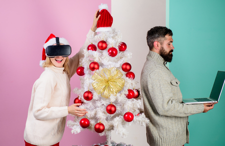 Santa girl in virtual reality glasses while Man with laptop beside christmas tree.
