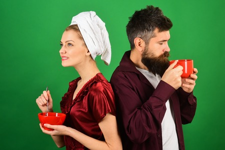 Couple, relationship, love, romantic, affection, lifestyle concept - loving couple having breakfast at home. Husband and wife have breakfast together. Romantic couple isolated on green background. 版權商用圖片