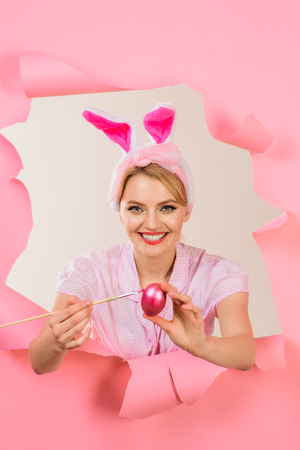 Happy easter! Egg hunt. Woman with fake bunny ears. Easter day concept. Painting eggs. Woman painting eggs. White bunny. Bunny ears. Through paper. Breaking paper. Sale. Discount.