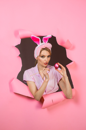 Sexy woman in Easter bunny ears. Festive bunny&eggs season. Easter, holidays, tradition concept. Lovely woman coloring egg through paper hole. Pretty girl preparing for Easter. Girl paints easter egg. Stockfoto
