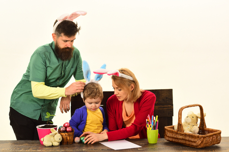 Easter family with color easter eggs on isolated background, space for text. Happy family with fake bunny ears sit on wood table with Easter eggs.