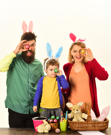 Easter family with color easter eggs on isolated background, space for text. Easter family with fake bunny ears. Happy family preparing for Easter. Banco de Imagens