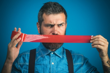 Serious bearded worker with mouth covered by red adhesive tape. Casual man wrapping duct tape over his mouth. Businessman with surprised face, mouth sealed insulating tape. Man with mouth taped closed Banco de Imagens