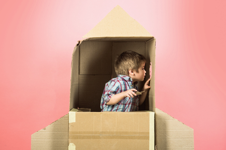 Childhood, dream, imagination concept - adorable boy plays in astronaut, looks in illuminator cardboard space rocket. Kid plays home with cardboard rocket ship. He imagining he is in space with stars. Foto de archivo