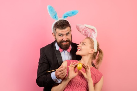 Family celebrate Easter Day. Happy couple. Happy holidays in family. Couple painting eggs for Easter. Decorating eggs ideas. Holidays. Spring holidays. Season. Bunny ears. Man with bunny ears.