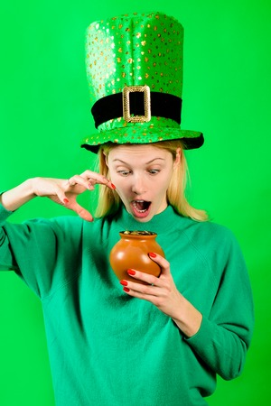 Green top hat. Surprised girl in Leprechaun costume holds pot with gold. Leprechaun. Pot with gold. Green leprechaun. Green hat with clover. Saint Patrick's Day. Traditions of Saint Patrick Day.