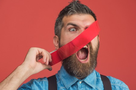 Scared bearded man glued his face insulating tape. Casual man in denim shirt with tape covering his face. Man with red duct tape. Attractive manager, businessman with face covered by red adhesive tape