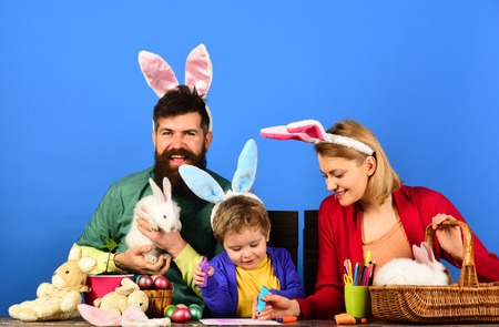 Easter family with color easter eggs on blue isolated background, space for text. Father and kid painting Easter eggs. Rabbit's family with bunny ears. Stock Photo - 118622865