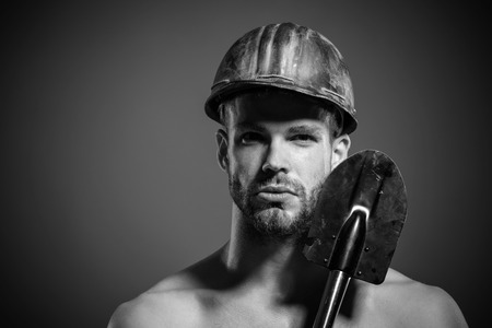 Male construction worker in hart hat holds spade. Construction, work and mining concept - sexy muscular builder or miner wears protective helmet holds shovel. Copy space in upper corner. Black & white Фото со стока