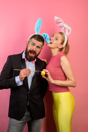Family celebrate Easter. Happy couple with bunny ears. Happy couple painting eggs for Easter. Decorating eggs. Bunny ears. Happy moments and Easter celebration concept. Lovely couple in rabbit costume