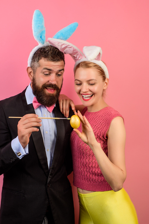 Family celebrate Easter. Lovely couple in rabbit costume. Happy couple with bunny ears. Happy couple painting eggs for Easter. Decorating eggs. Bunny ears. Happy moments and Easter celebration concept Imagens