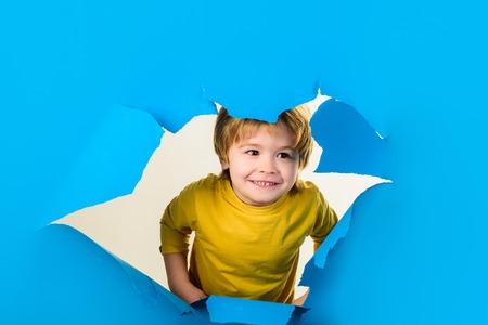 Boy looking through paper. Boy through paper. Happy kid. Season sale. Breaking paper. Sale. Discount. Season sales. Kids. Advertising. Happy childhood. Smile. 写真素材 - 118877735