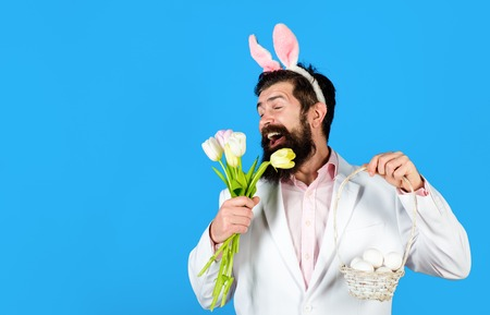 Bearded man in suit holds basket with eggs. Rabbit man in bunny mask with flower. Happy Easter. Preparation for Easter. Spring holiday. Spring flower. Easter bunny costume. Easter celebration concept. Stock Photo