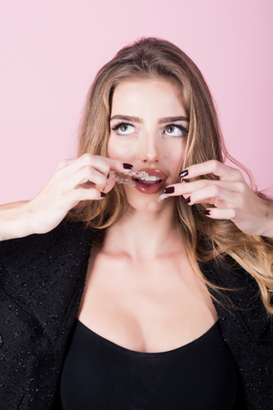 Gorgeous young woman holds transparent orthodontic device. Close-up of woman holds transparent teeth aligner in hand. Teeth care. Orthodontic devices. Woman putting transparent retainer in teeth.