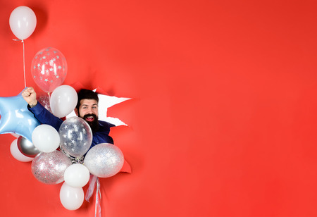 Bearded man with balloons looks through hole in paper. Successful businessman with balloons. Birthday, preparation to party, celebration. Happy bearded man with bunch of balloons is inviting to party.