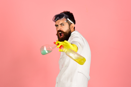 Screaming bearded man in uniform, rubber gloves holding cleanser spray with cleaning fluid. Cleaning, housekeeping concept - man from professional cleaning service. Copy space for advertise detergents