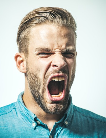 Man with angry screaming face. Portrait of angry screaming man. Furious bearded businessman shouting. Feeling angry. Excited attractive bearded macho in denim shirt screams. Unleashing his emotions.